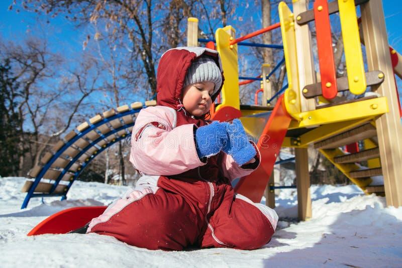 Маленький младенец играет в спортивной площадке в зиме стоковое изображение rf