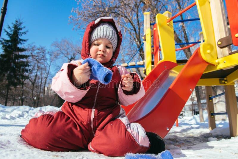 Маленький младенец играет в спортивной площадке в зиме стоковое фото