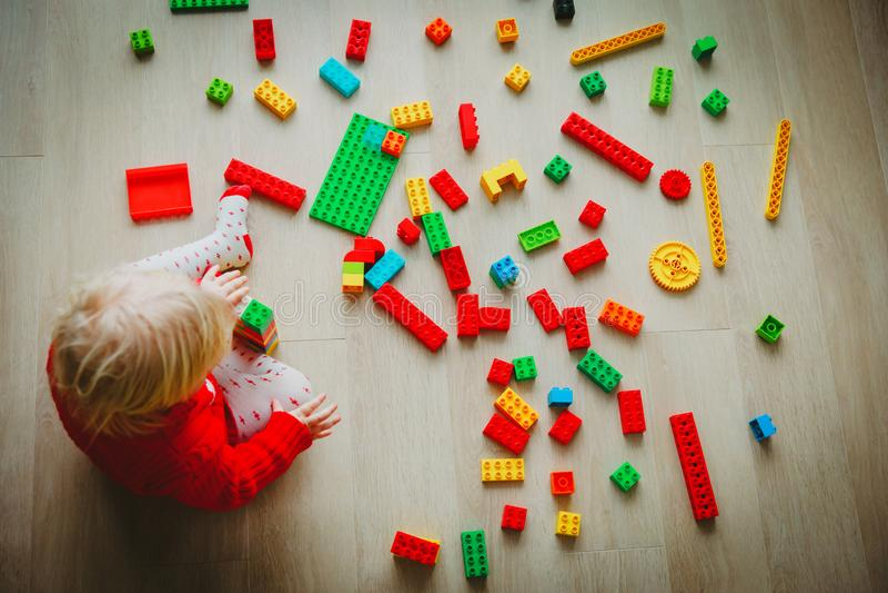 Маленький младенец играя с красочными пластичными блоками стоковое изображение