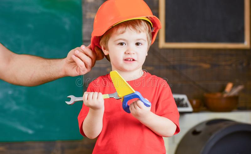Маленький папа порции работника в мастерской Ребенк играя с ручной пилой и гаечным ключом игрушки Отец держа защитный шлем дальше стоковое фото rf