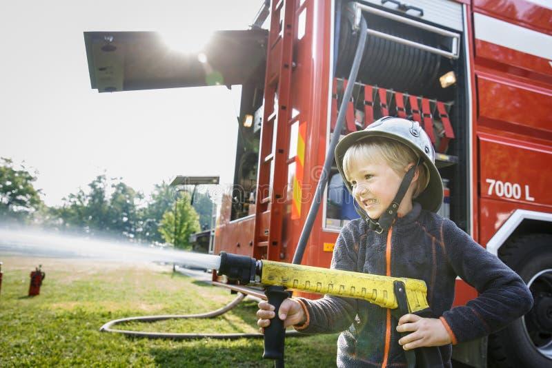 Маленький пожарный держа сопло firehose и брызгая воду стоковое изображение