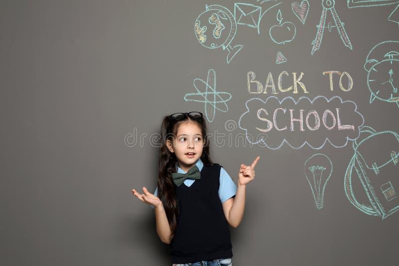 Маленький ребенок в равномерных близко чертежах с текстом НАЗАД К ШКОЛЕ на серой предпосылке стоковые изображения