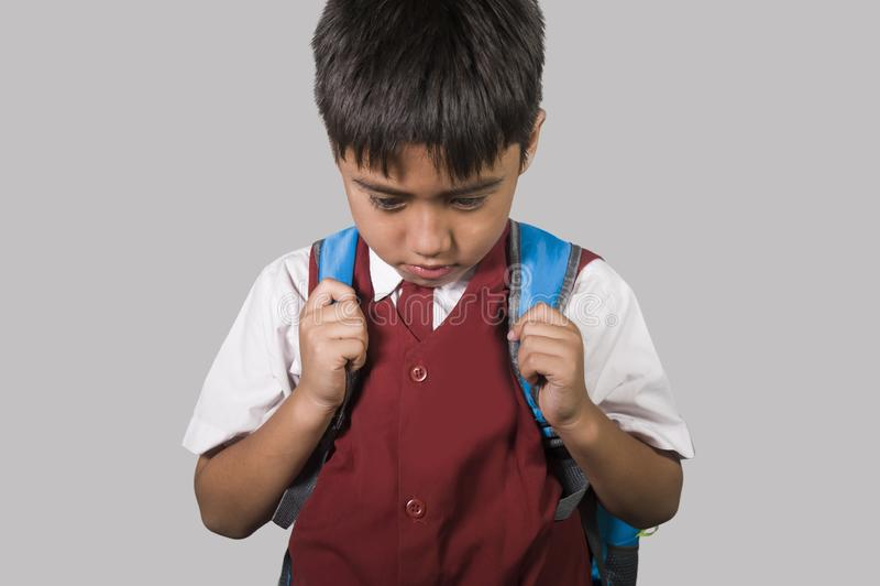 Маленький ребенок в школьной форме чувствуя унылый и подавленный смотреть вниз с вспугнутой и смущенной жертвы задирать и злоупот стоковая фотография