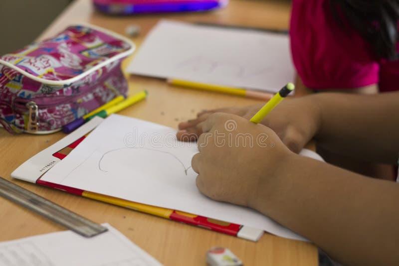 Маленький ребенок делая эскиз к на белом листе стоковая фотография rf
