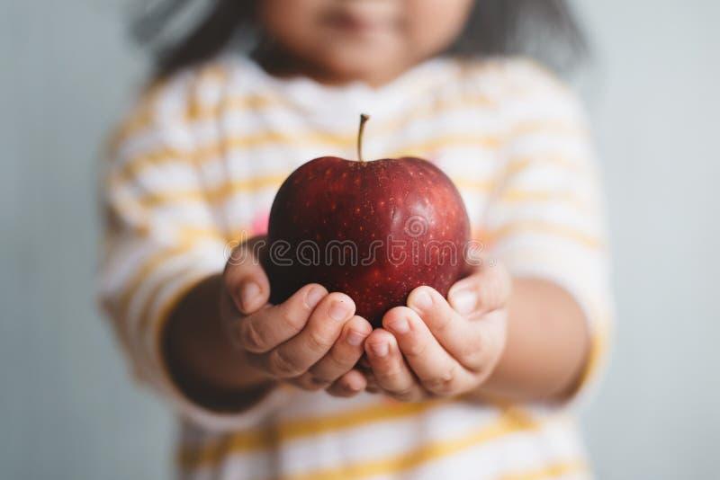 Маленький ребенок, держащий в руке красное яблоко с селективной и мелкой глубиной размытого изображения поля стоковые изображения