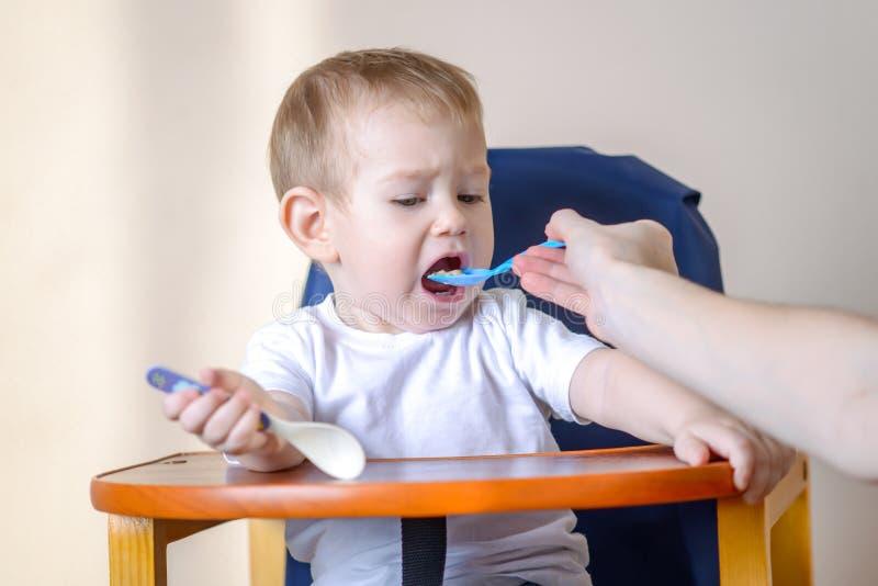 Маленький ребенок ест открытие его рта широко сидя на стуле в кухне Питания мамы держа ложку каши стоковое фото