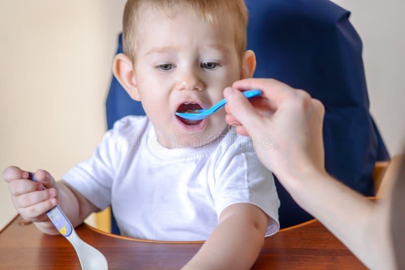 Маленький ребенок ест открытие его рта широко сидя на стуле в кухне Питания мамы держа ложку каши стоковые фотографии rf