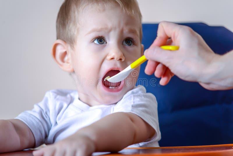 Маленький ребенок ест открытие его рта широко сидя на стуле в кухне Питания мамы держа ложку каши стоковые фото