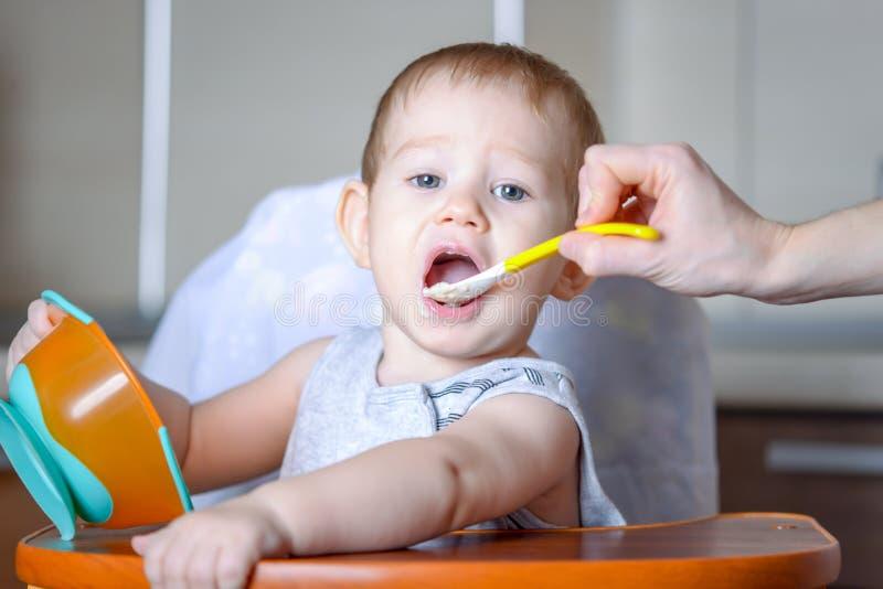Маленький ребенок ест открытие его рта широко сидя на стуле в кухне Питания мамы держа ложку каши стоковые изображения