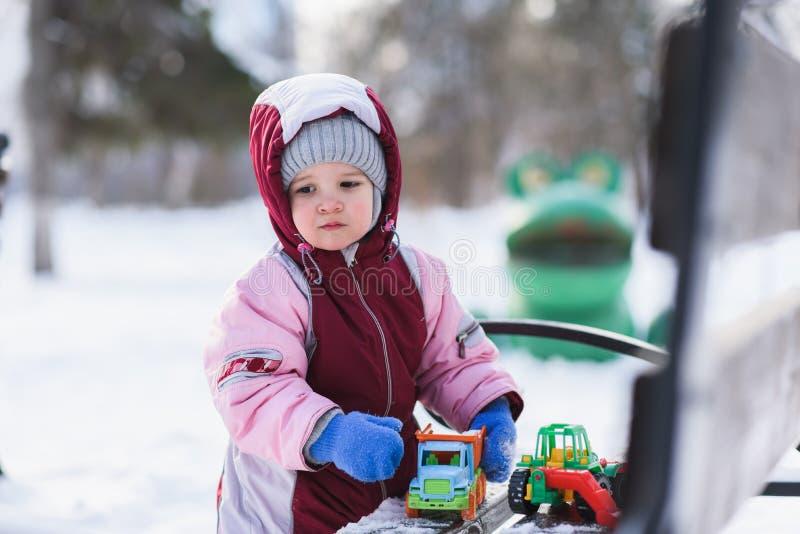 Маленький ребенок играет с игрушками в зиме в парке стоковое фото