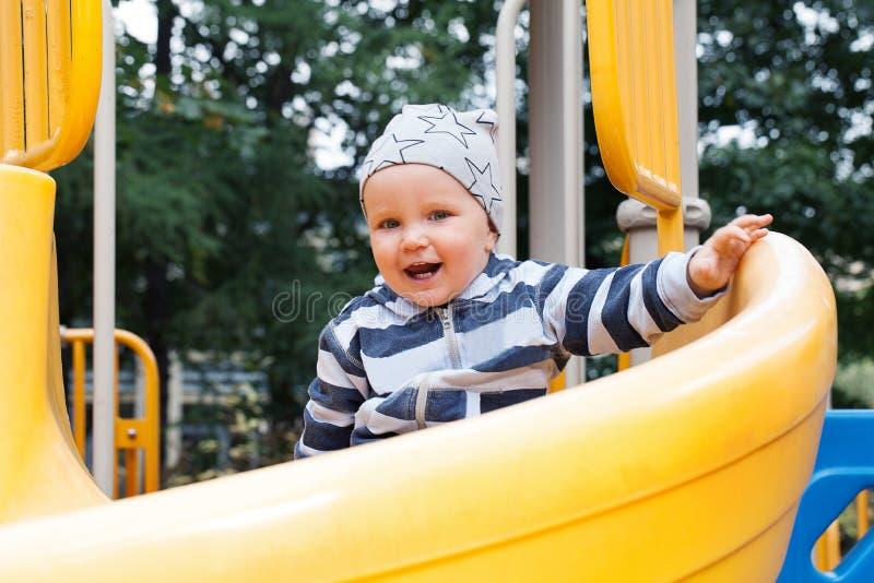 Маленький ребенок имея потеху на спортивной площадке outdoors стоковая фотография rf