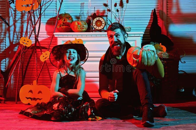 Маленький ребенок и отец высекают тыкву для партии хеллоуина Маленький ребенок и отец одеванные для партии костюма halloween стоковая фотография rf