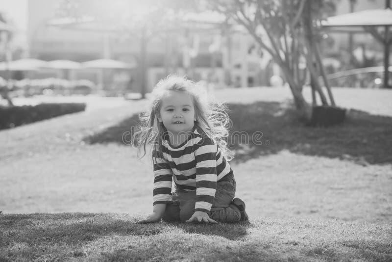 Маленький ребенок при счастливая сторона имея потеху на зеленом луге стоковая фотография