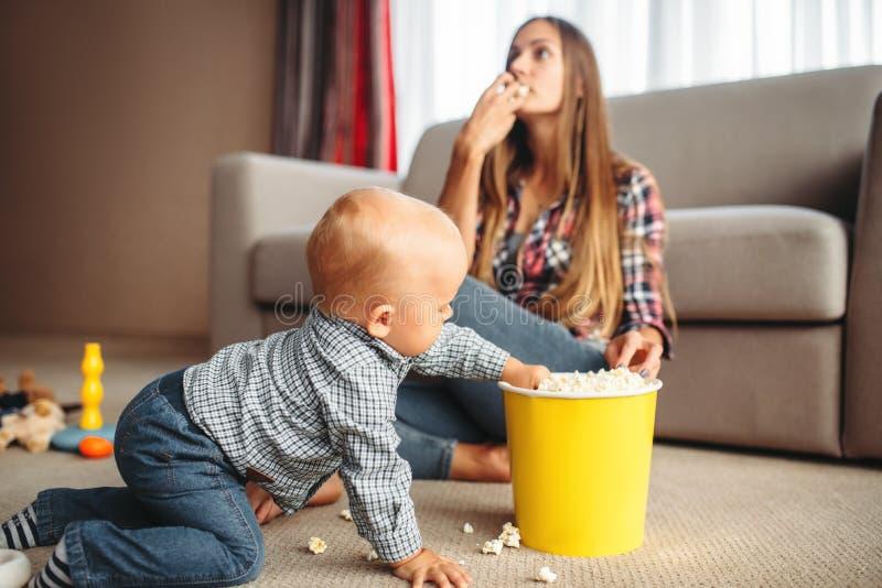 Маленький ребенок разлил попкорн, проблемы материнства стоковое фото