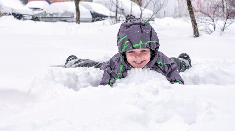 Маленький ребенок смотрит из снега или частей льда Ребенок p стоковое изображение