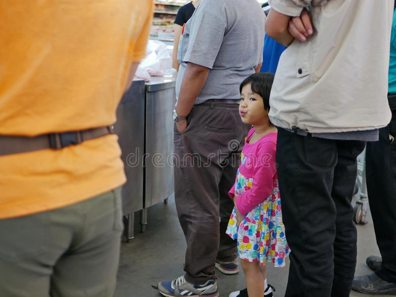Маленький ребенок уча ждать терпеливо в очереди как все другие взрослые, весить покупая сырцовые продукты и высчитать цены стоковое изображение