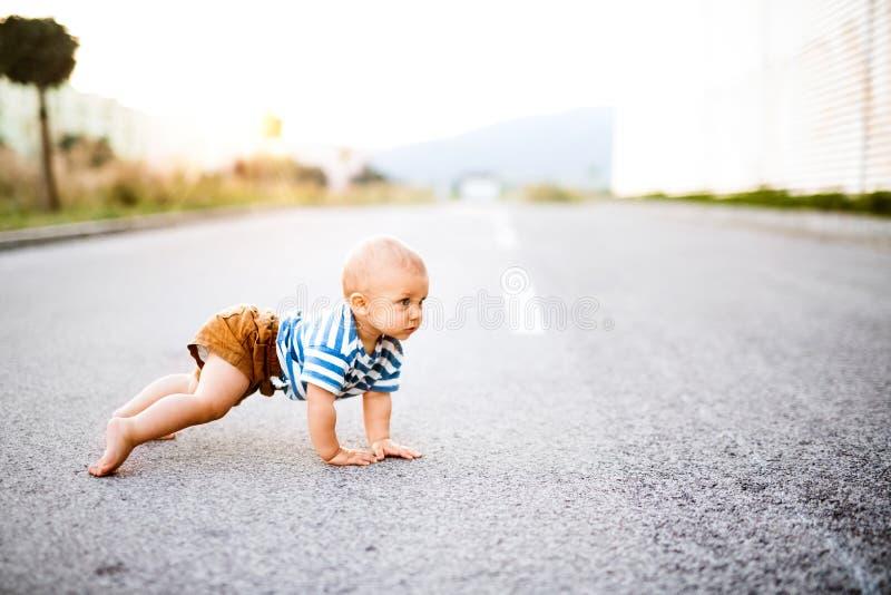 Маленький ребёнок вползая снаружи на дороге стоковое фото rf