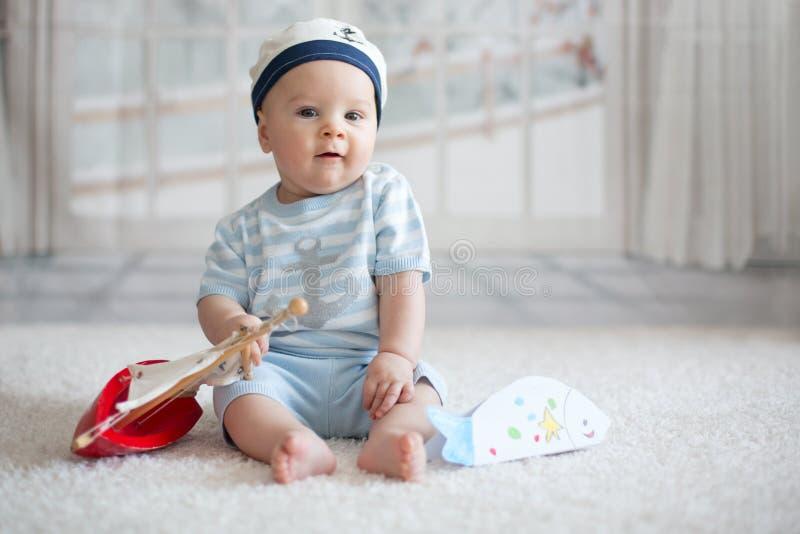 Маленький ребёнок, играющ с меньшими шлюпкой и маленькими рыбами на hom стоковое фото rf