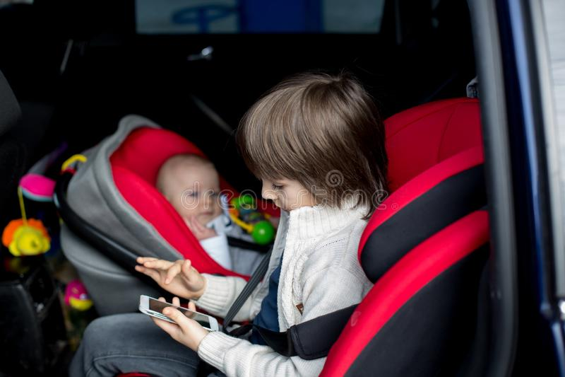 Маленький ребёнок и его более старый брат, путешествуя в автокреслах, g стоковые фотографии rf