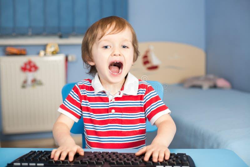 Маленький ребёнок кричащий печатая на машинке на клавиатуре стоковая фотография rf