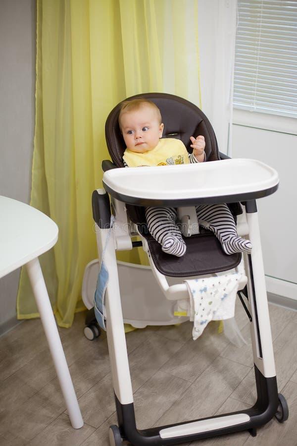 Маленький ребёнок сидя в стуле для подавать и еды специальное печенье для младенцев Кухня стоковая фотография
