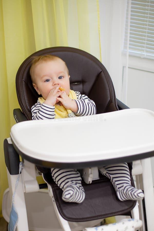 Маленький ребёнок сидя в стуле для подавать и еды специальное печенье для младенцев Кухня стоковое изображение rf