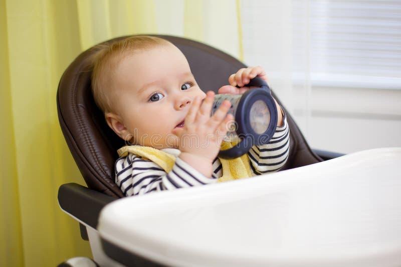 Маленький ребёнок сидя в стуле для подавать и питьевой воды с подавая бутылкой Кухня стоковое фото rf