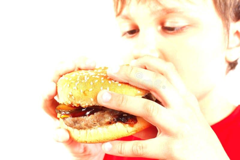 Маленький смешной мальчик есть вкусный гамбургер на белой предпосылке Весьма тонизированный конец вверх стоковое фото