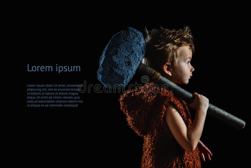 Маленький смешной мальчик неандерталец или cro-Magnon Старый троглодит с огромной осью изолирован на черноте Текст с космосом экз стоковые изображения