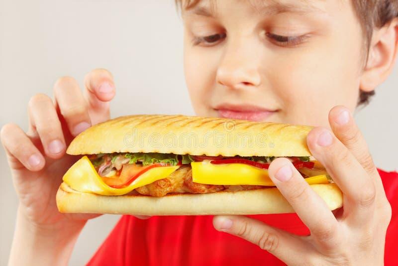 Маленький смешной мальчик с вкусным cheeseburger на белом конце предпосылки вверх стоковое изображение