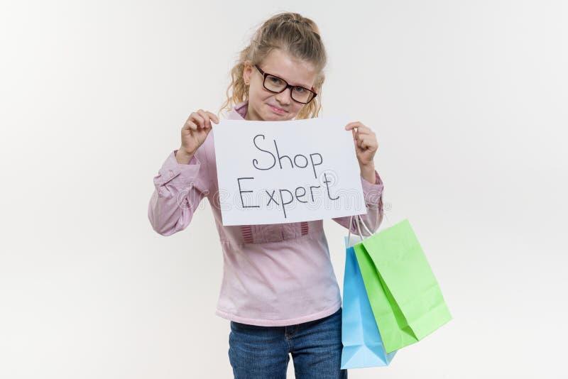 Маленький специалист по магазина, девушка ребенка с хозяйственными сумками держа белый лист бумаги со специалистом магазина текст стоковые изображения