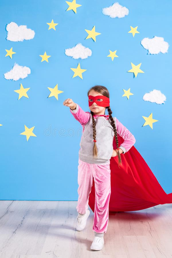Маленький супергерой детских игр Оягнитесь на предпосылке яркой голубой стены стоковая фотография