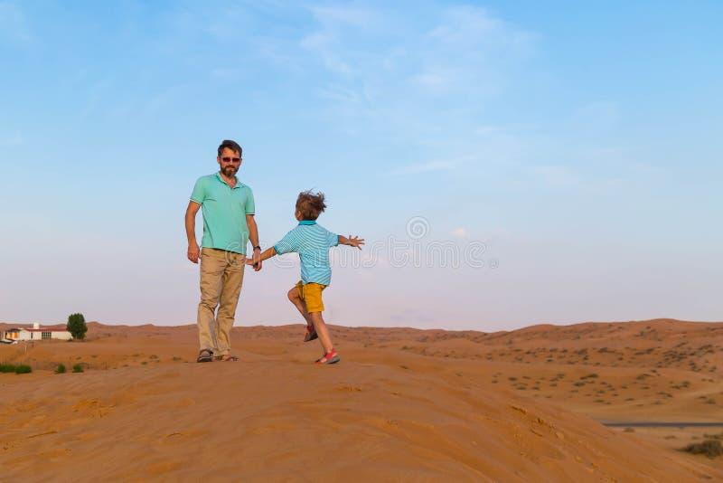 маленький сын бега на встрече к отцу на дюнах в горячей пустыне стоковые фото