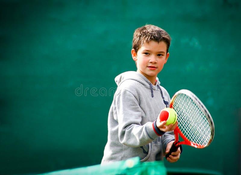 Маленький теннисист на запачканной зеленой предпосылке стоковые изображения rf