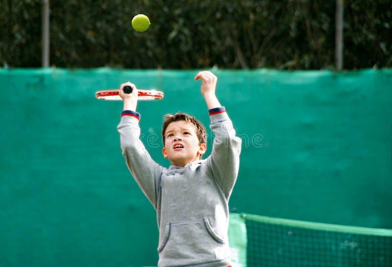 Маленький теннисист на запачканной зеленой предпосылке стоковые фото