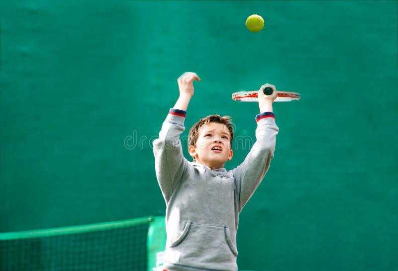 Маленький теннисист на запачканной зеленой предпосылке стоковая фотография