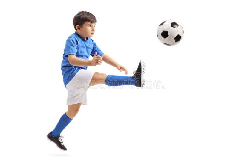 Маленький футболист пиная футбол в средний-воздухе стоковое изображение