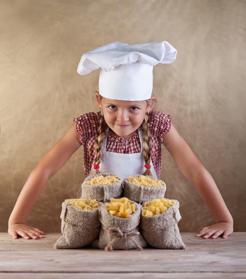 Маленький шеф-повар с разнообразием макаронных изделий в мешках стоковые изображения