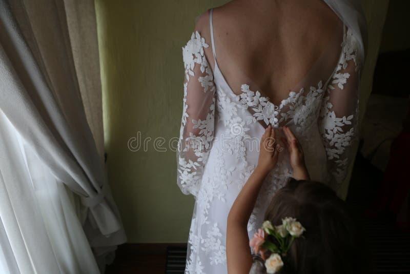 маленький bridesmaid застегивает платье свадьбы схематический назад стоковая фотография rf