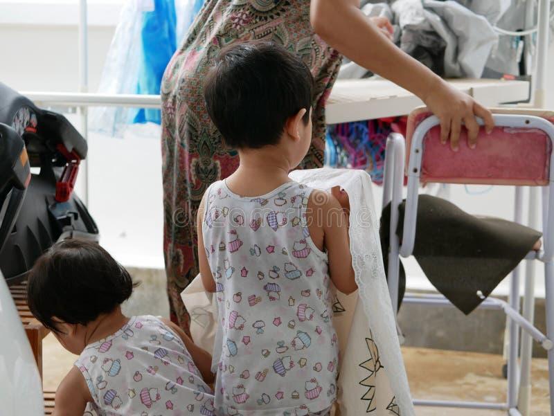 2 маленьких азиатских ребёнка нося ткань таблицы их мать для того чтобы повиснуть ее и получить ее сухой после мыть для стоковое изображение rf