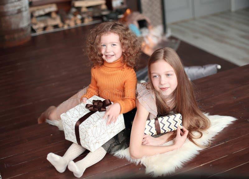 2 маленьких сестры с подарочными коробками, сидя на поле в уютной живущей комнате стоковая фотография