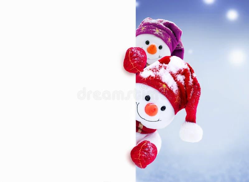 2 маленьких снеговика девушка и мальчик в крышках и шарфах на снеге в зиме Предпосылка со смешным снеговиком стоковое изображение