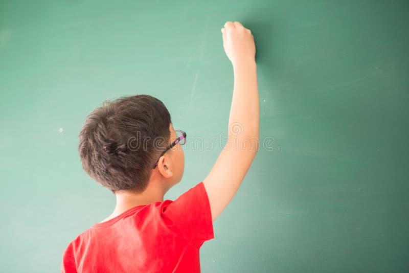 Маленькое азиатское сочинительство мальчика на пустой зеленой школе доски стоковые фото