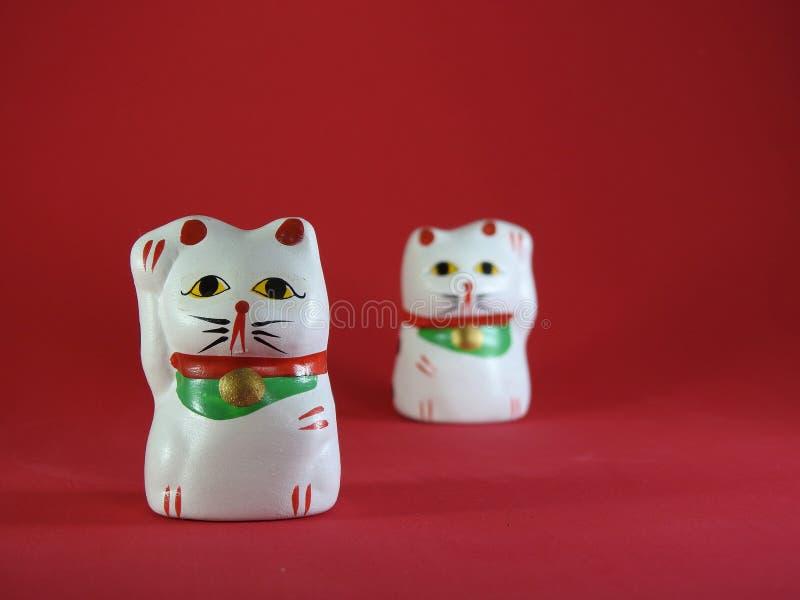 2 маленькое Maneki Neko, японские удачливые коты, талисман которые приносят удачи стоковая фотография rf