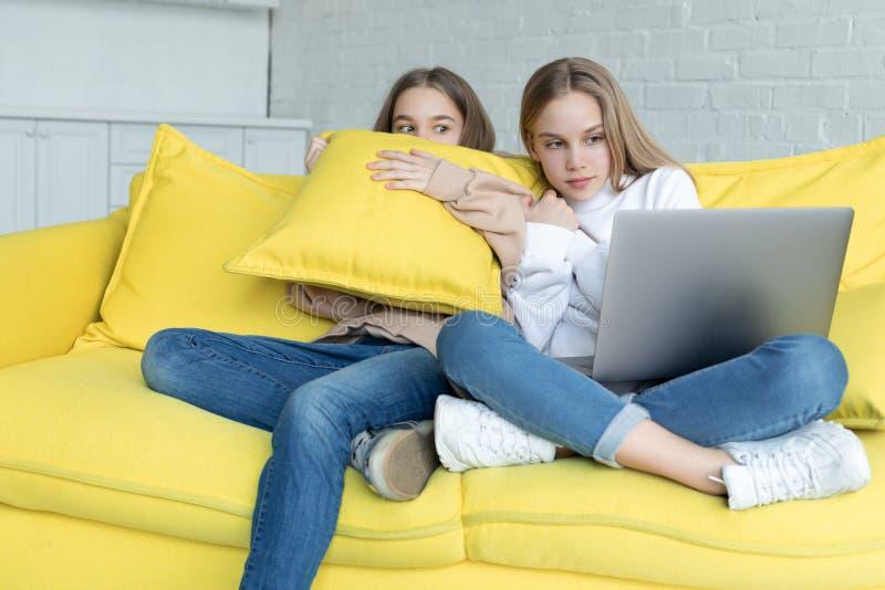 2 маленькой девочки в случайных одеждах сидя совместно на желтой софе дома стоковое фото