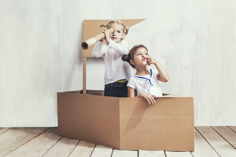 2 маленькой девочки детей самонаводят в капитанах игры корабля картона стоковые фотографии rf