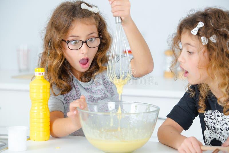 2 маленькой девочки имея выпечку потехи стоковая фотография rf