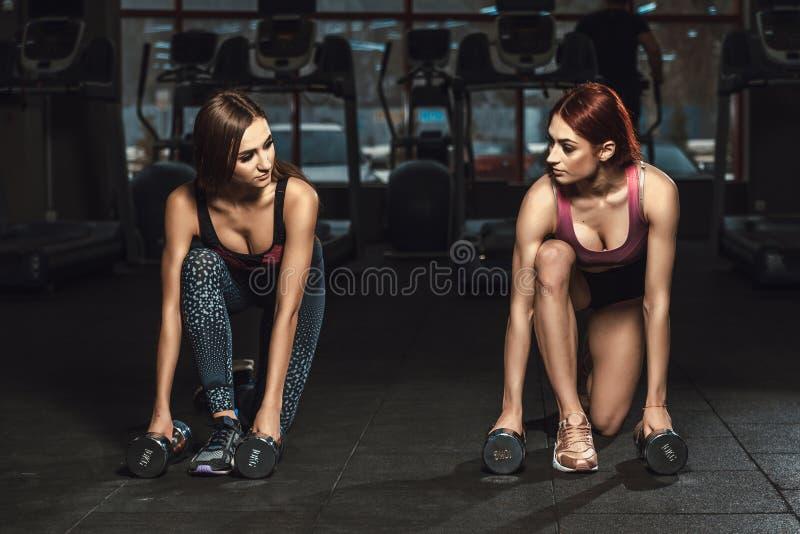 2 маленькой девочки красивых фитнеса sporty делая выпады с гантелями в спортзале смотря один другого стоковое изображение rf