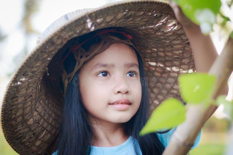 Маленькой девочки съемки портрета шляпа фермера близкой поднимающей вверх азиатской нося в g стоковая фотография rf