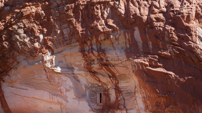 Малое окно в стороне скалы белого песчаника исчертило с красным цветом с нуля выше стоковое фото rf